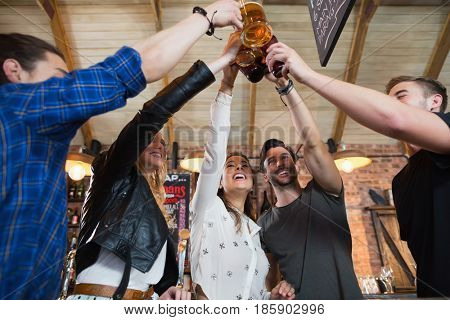 Cheerful friends toasting beer bottles and mugs in bar