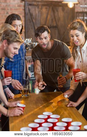 Friends looking at ball while man playing beer pong on table in bar