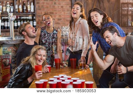 Friends playing beer pong on table in bar