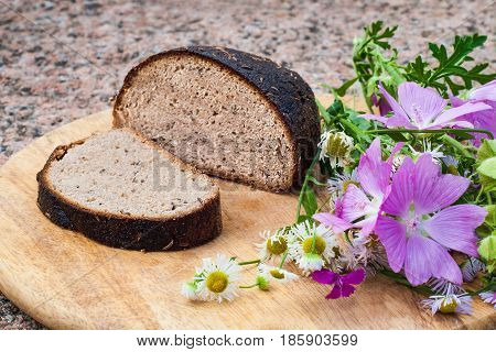 Loaf of rye bread with caraway seeds and wild flowers on cutting board