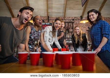 Young friends playing beer pong game on table in bar