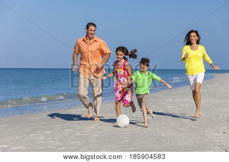 A happy family of mother, father and two children, son and daughter, running playing soccer or football in the sand of a sunny beach