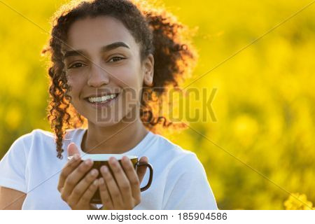 Beautiful happy mixed race African American girl teenager female young woman smiling drinking coffee or tea outdoors