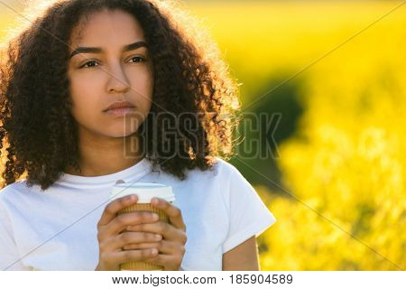 Beautiful thoughtful mixed race African American girl teenager female young woman smiling drinking takeaway coffee outside