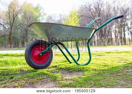 Wheelbarrow to work in the garden standing on a green grass