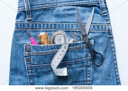 Close Up Of Seam Ripper Thread Centimeter Tape Thimble Pins Scissors In Pocket Of Blue Jeans On White Background Top View.