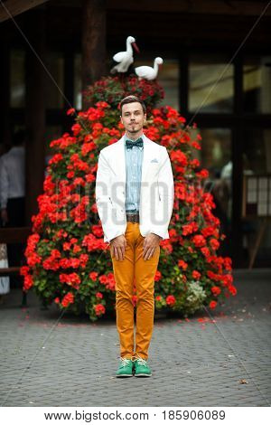 Man in yellow trousers stands straight in the front of a red bush