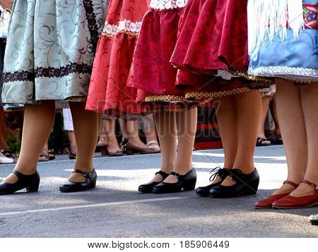 Folk dancers standing in traditional pleated skirts