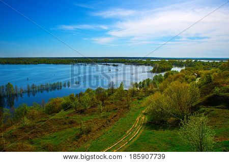 Beautiful spring landscape from high hill. Amazing view of the floods from the hill. Europe. Ukraine. Impressive blue sky with white clouds