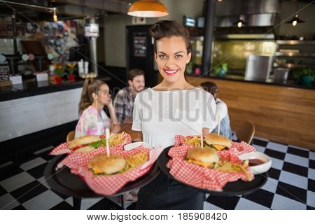 Portrait of waitress serving burger while customers sitting in restaurant