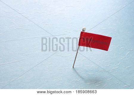 pin with a red Entrepreneur flag on blue textured surface