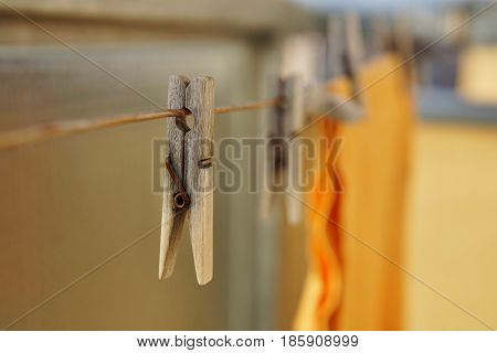 Wooden clothespin (peg) hanging on the balcony string as a symbol of washing clothes at home