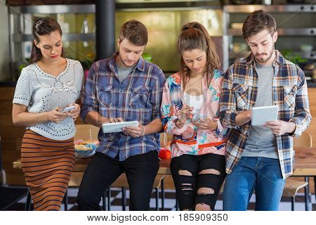 Friends using mobile phones and digital tablets while standing in restaurant