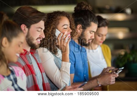 Young friends using mobile phones in pub