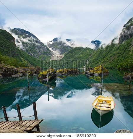 Fishing boat on a still lake in Norway and high mountains in background. Bondhusvatnet