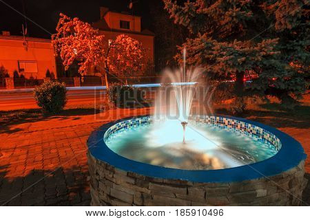 Small fountain in night city. Red street light and flowing water
