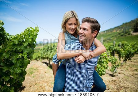 Smiling young couple piggybacking at vineyard against blue sky
