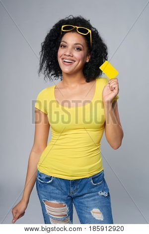 Happy smiling mixed race african ethnicity woman holding credit card standing relaxed isolated on grey background