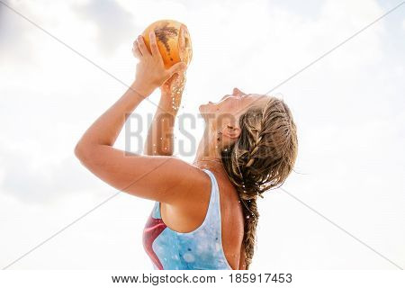 A Woman Drinks Coconut At The Seashore At Sunset