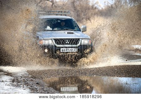 KHABAROVSK RUSSIA - MARCH 25 2017: Mitsubishi Pajero Sport on dirt road in early spring making splashes from a big puddle