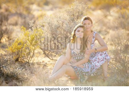 Portrait Of A Young Mother And Her Daughter In Desert Of Red Rock