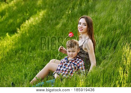 Mother and son sitting on grass holding flowers . Outing