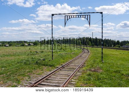 Railroad tracks going into the distance towards the forest and village in summer sunny day.