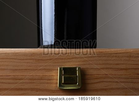 Closeup of a wine bottle standing on a wooden case. Horizontal format with copy space.