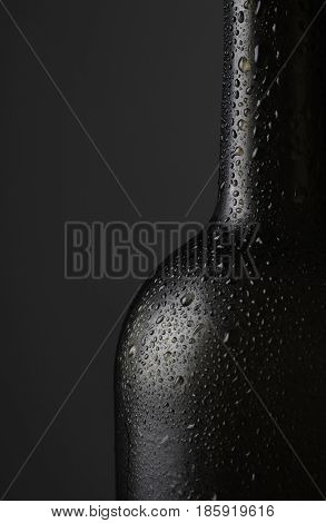 Closeup of a red wine bottle covered with water droplets against a dark background with copy space.
