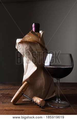Closeup of a wine bottle in a paper bag on a wooden table with a glass and corkscrew.