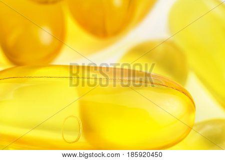 Yellow capsules omega 3 fatty acid fish oil on heap macro image.