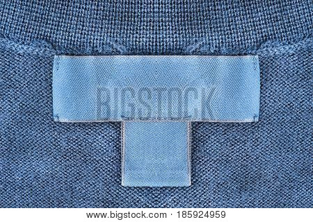 Blank clothes label on blue knitted background closeup