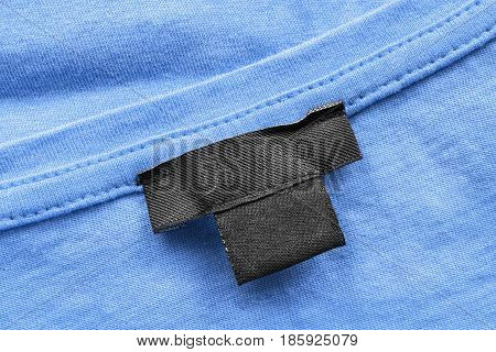 Black blank clothes label on blue cloth as a background