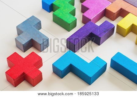 The concept of creative logical thinking or problem solving. Abstract Background. Different colorful shapes wooden blocks on beige background. Geometric shapes in different colors.