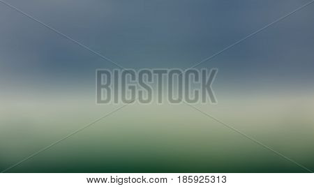 Grey blurred clouds atop the fog spreading the green grass background