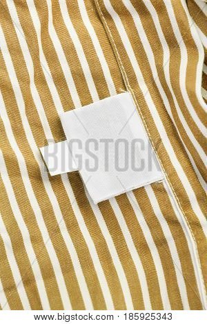 Blank clothes label on striped yellow cotton as a background
