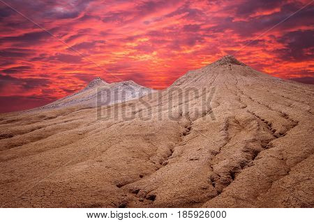 Sunset over muddy volcanoes, Buzau county, Romania. Active mud volcanoes landscape in Europe.