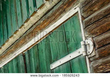 Painted white old iron hinges on the green gates to the garage.