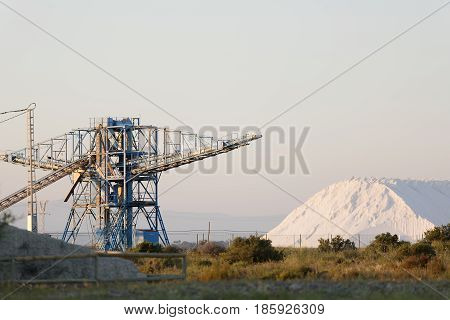 Salt mountain next to the cranes in the salt pans of Santa Pola province of Alicante in Spain.