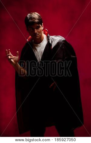 The sexy man is wearing a vampire outfit.