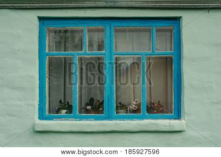 Blue wooden window of an old private house whose walls are painted in light green color. The old building. Plastered walls.