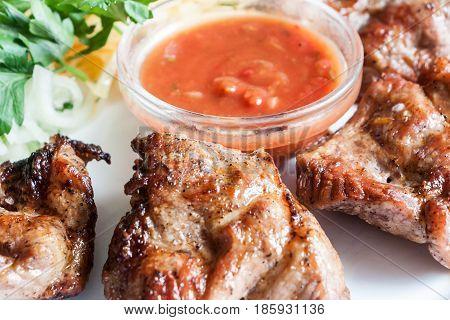 Pork Shish Kebab With Tomato Sauce On A White Plate