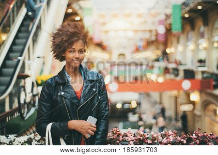 Beautiful black teenage girl in leather jacket and with smart phone is standing in huge multistorey shop attractive mixed young female with curly afro hair during shopping with copy space for message