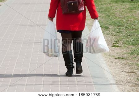 the girl goes along the road with packages in hands in clear day