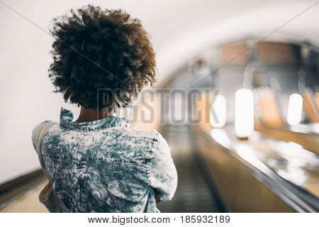 Rear view of black teenage girl with curly afro hair in trendy blue shirt standing on descending escalator in subway with copy space for young advertising text message or promotional content