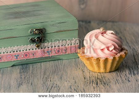 Cake with cream on a wooden table with a vintage casket