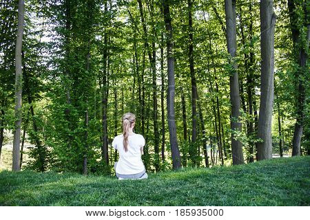 A girl in a white t-shirt sits and stares into the green forest. Rear view.