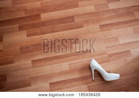 Background, one white shoe of the bride, lies on the plank floor
