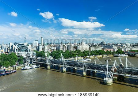 London panorama with Hungerford Bridge over Thames River (Charing Cross Bridge) Victoria Embankment and urban architectures. United Kingdom