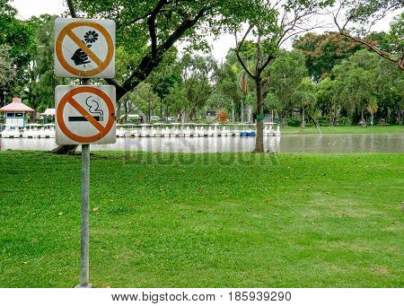 The signs Do not pick flower metal sign orange cycle color and Label no smoking metal sign red cycle color in the park.